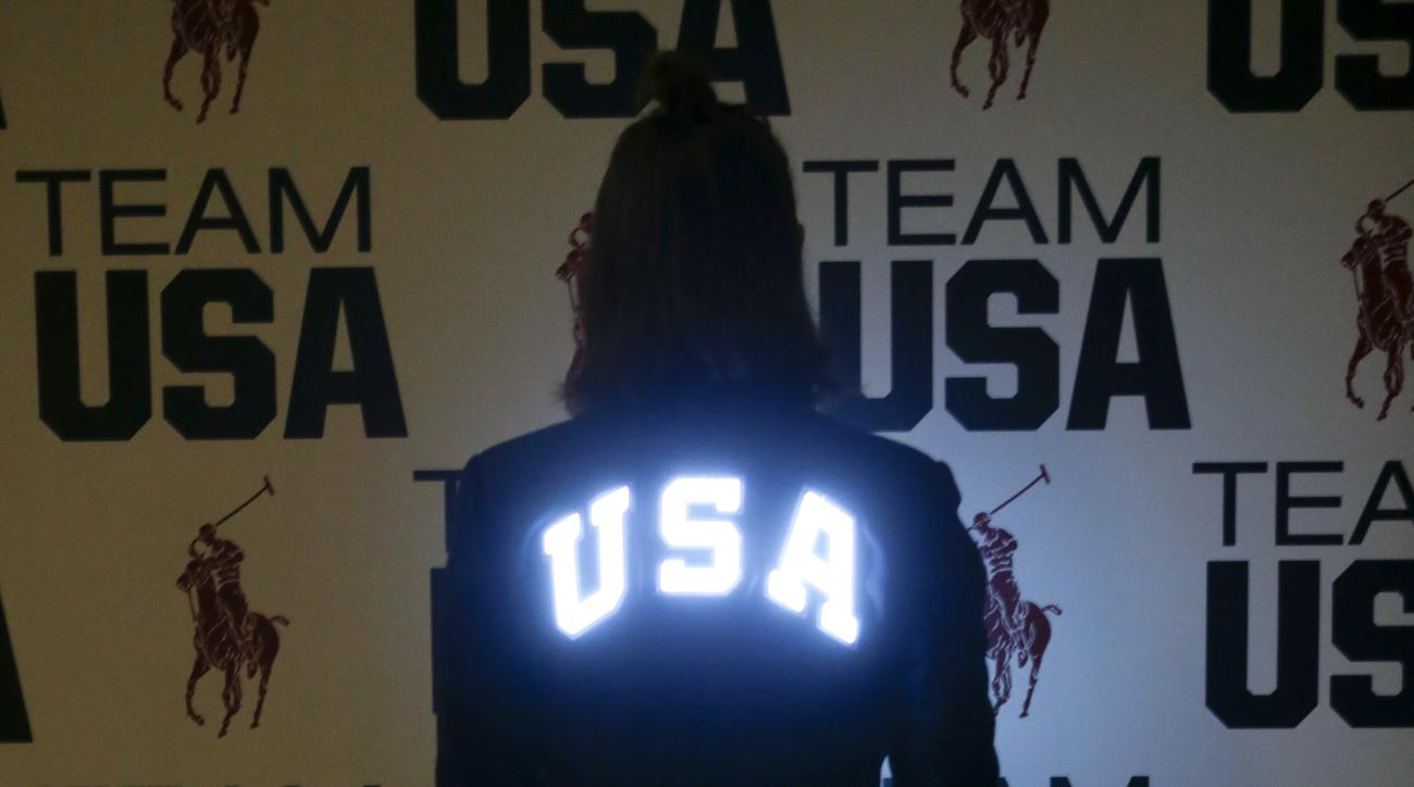 In this July 25, 2016 photo, Olympian Kelly Hurley models a custom-fitted Polo Ralph Lauren jacket at the United States Olympic Committee processing station in Houston that features electroluminescent panels illuminating the US Olympic team symbol and the