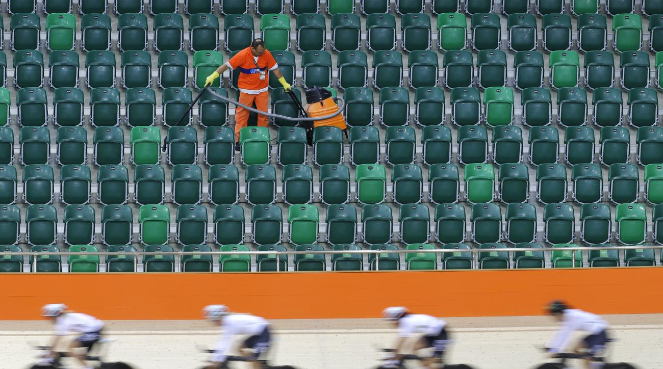 A worker vacuums spectator seating as members of the German women's track cycling team round the track during a training session inside the Rio Olympic Velodrome in advance of the 2016 Olympic Games in Rio de Janeiro, Brazil, Thursday, Aug. 4, 2016. (AP P