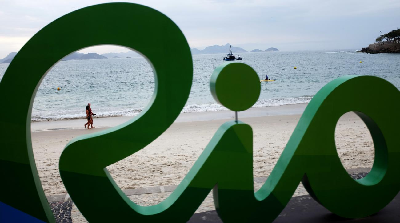 A couple walks along Copacabana beach ahead of the upcoming 2016 Summer Olympics in Rio de Janeiro, Brazil, Thursday, Aug. 4, 2016. The iconic Copacabana beach will be the starting point for the road cycling race, marathon swimming and triathlon competiti