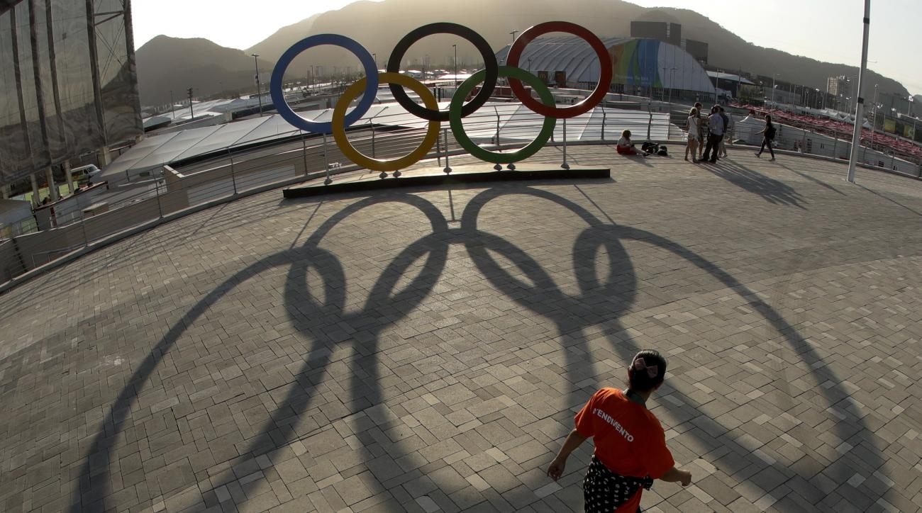 A worker walks past a set of Olympic rings in the Olympic Park ahead of the Rio 2016 Summer Olympics, in Rio de Janeiro, Brazil, Thursday, Aug. 4, 2016. (AP Photo/Charlie Riedel)