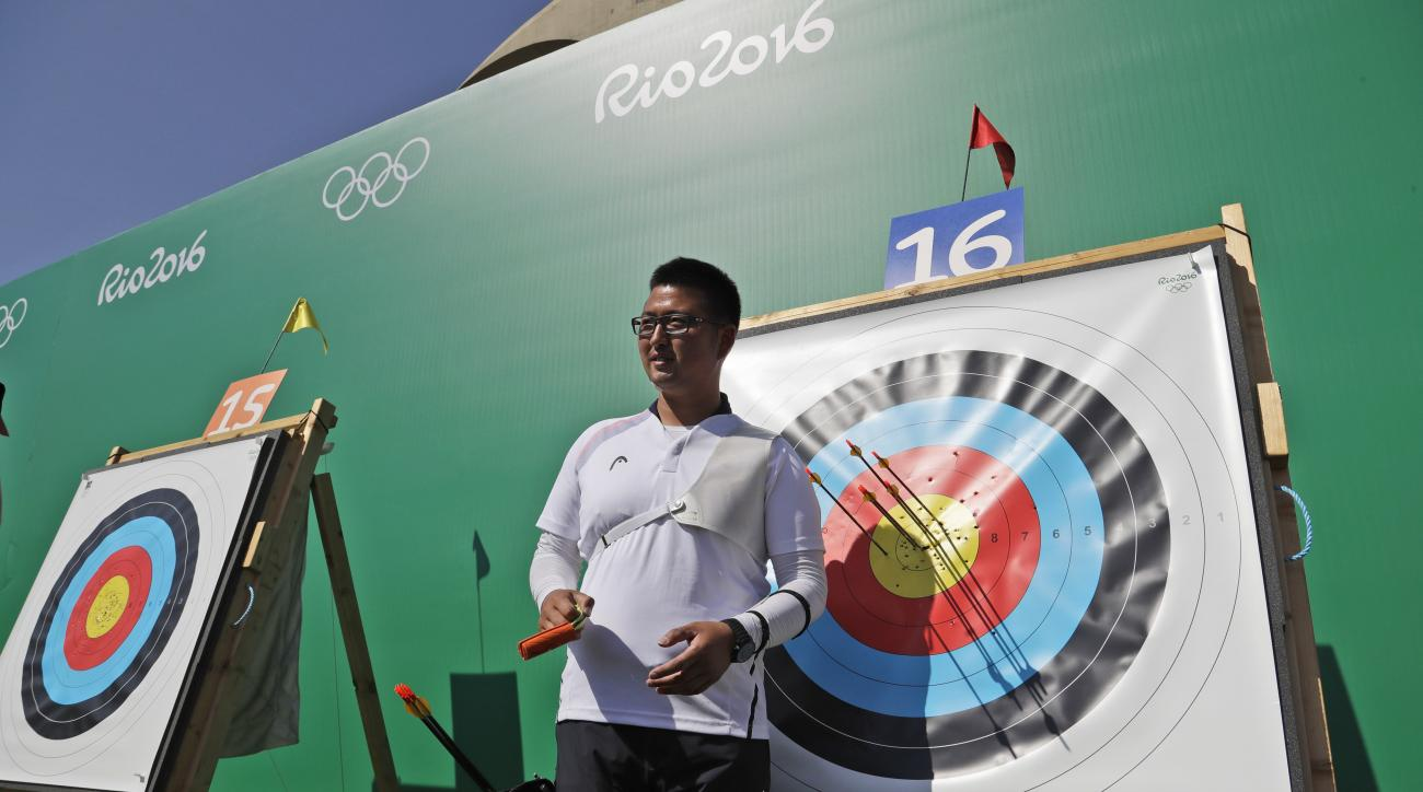 South Korea's Kim Woo-jin poses for photographers after setting a new record during an individual ranking round at the 2016 Summer Olympics in Rio de Janeiro, Brazil, Friday, Aug. 5, 2016. Woo-jin set a recurve world record with a score of 700 during the