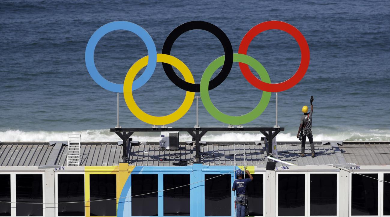 Workers install Olympic rings with the ocean as a backdrop during a training session at Copacabana beach volleyball arena at the 2016 Summer Olympics in Rio de Janeiro, Brazil, Friday, Aug. 5, 2016. (AP Photo/Marcio Jose Sanchez)