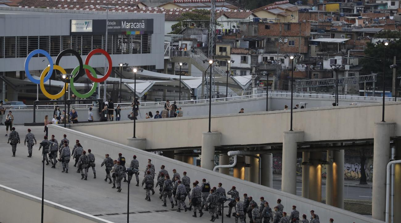 Soldiers pass by the Olympic rings in the Maracana Stadium prior to the opening ceremony for the 2016 Summer Olympics in Rio de Janeiro, Brazil, Friday, Aug. 5, 2016. (AP Photo/Jae C. Hong)