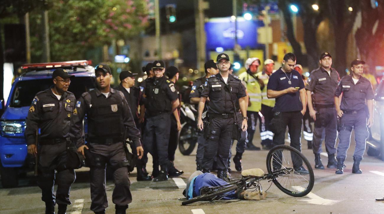 Police stand near the body of a man that was shot and killed near Maracana Stadium after the opening ceremony at the 2016 Summer Olympics in Rio de Janeiro, Brazil, Saturday, Aug. 6, 2016. (AP Photo/David J. Phillip )