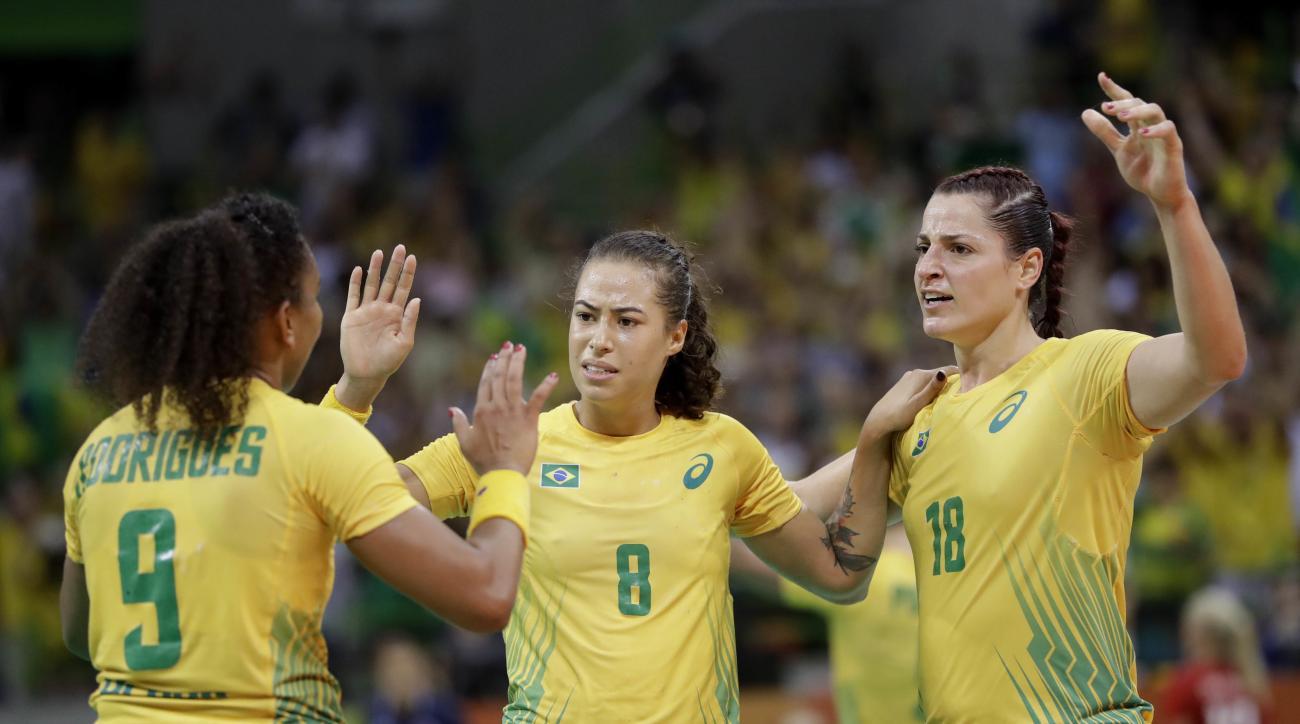 Brazil's Ana Paula Belo, from left, Brazil's Fernanda Franca Da Silva and Brazil's Eduarda Taleska celebrate after defeating Norway during the women's preliminary handball match between Norway and Brazil at the 2016 Summer Olympics in Rio de Janeiro, Braz