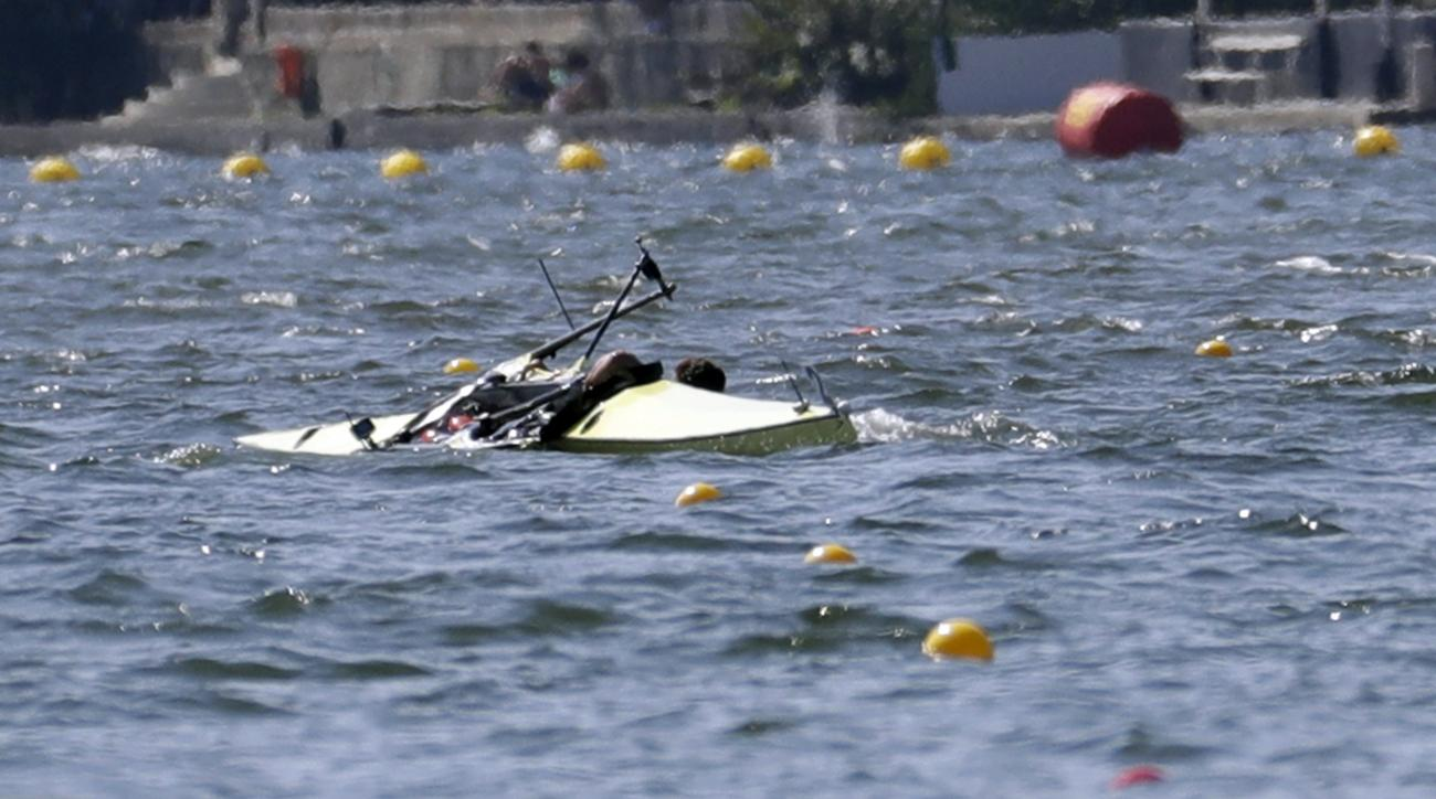 Milos Vasic and Nenad Bedik, of Serbia, capsize while competing in the men's pair heat during the 2016 Summer Olympics in Rio de Janeiro, Brazil, Saturday, Aug. 6, 2016. (AP Photo/Andre Penner)