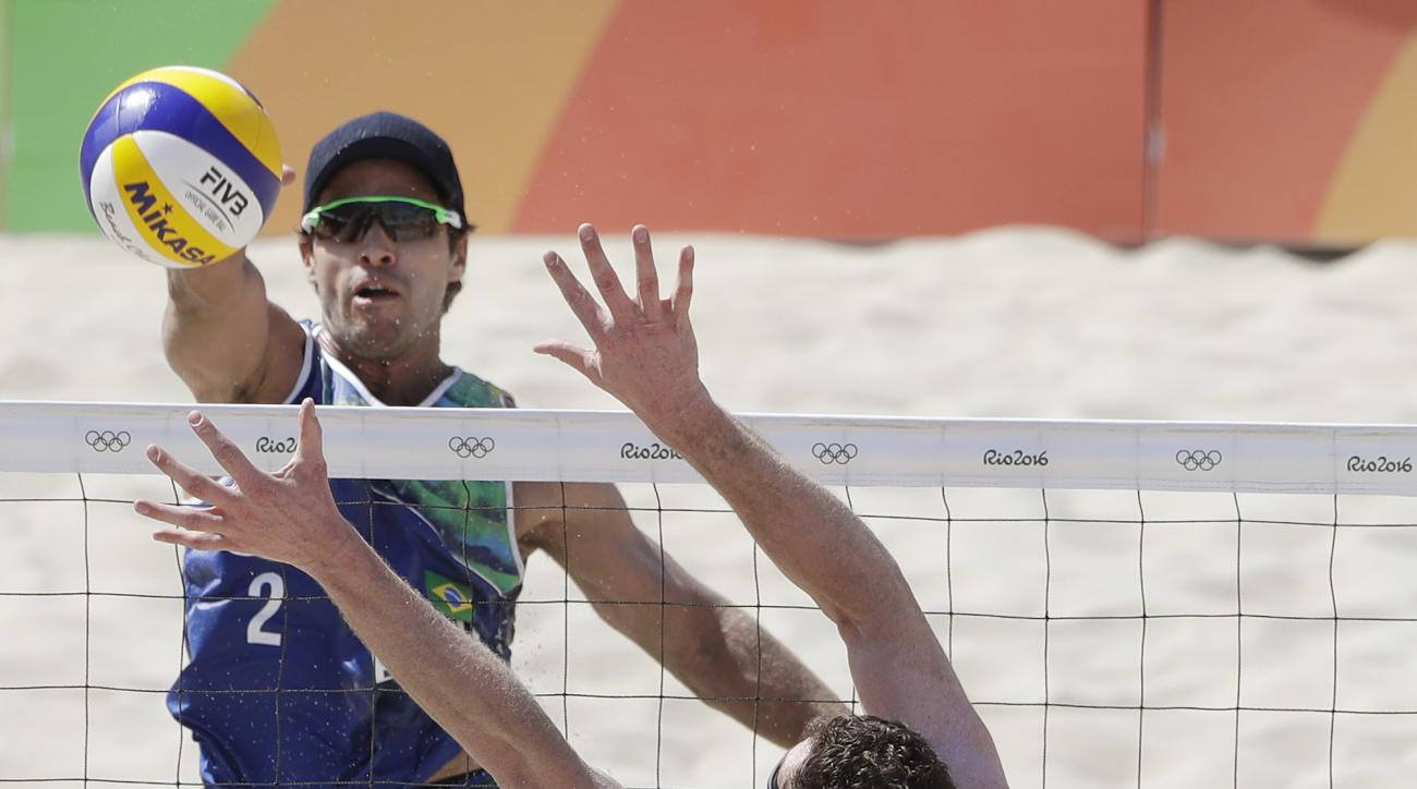 Brazi's Bruno Oscar Schmidt, top, hits over Canada's Josh Binstock during a men's beach volleyball match at the 2016 Summer Olympics in Rio de Janeiro, Brazil, Saturday, Aug. 6, 2016. (AP Photo/Marcio Jose Sanchez)