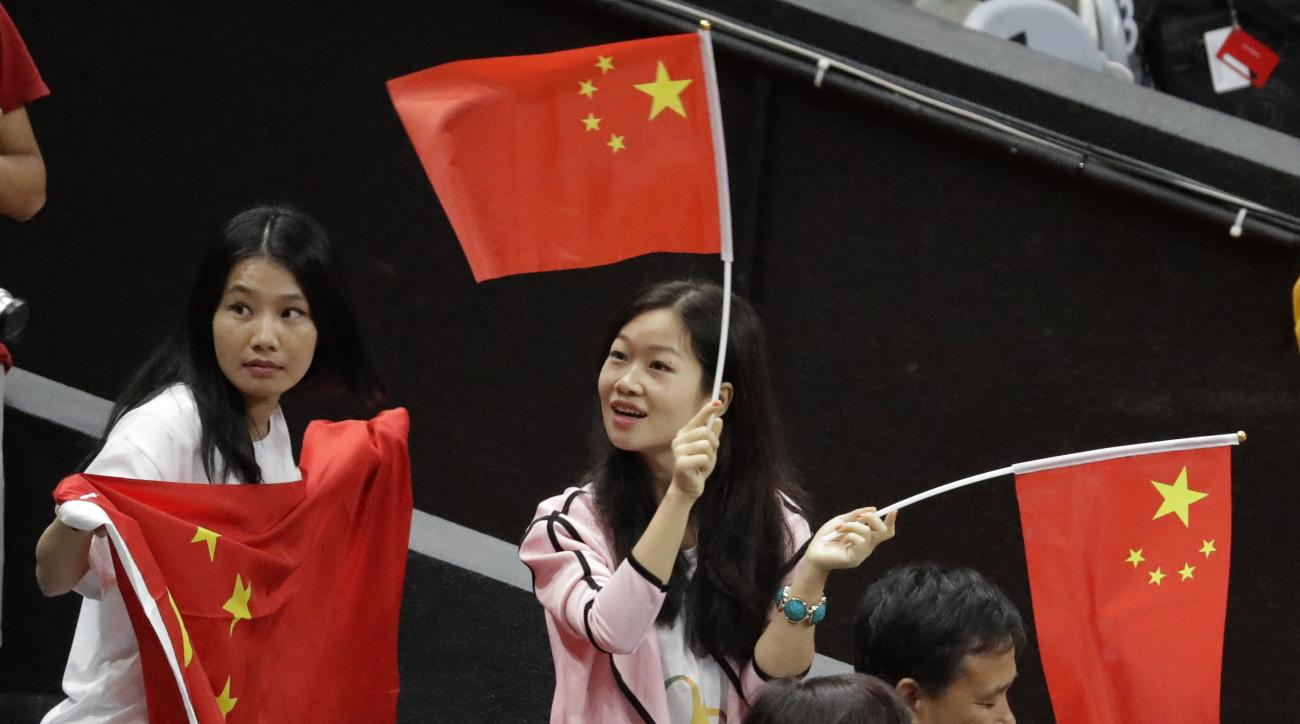Fans wave China's flag during a women's preliminary volleyball match between the Netherlands and China at the 2016 Summer Olympics in Rio de Janeiro, Brazil, Saturday, Aug. 6, 2016. (AP Photo/Jeff Roberson)