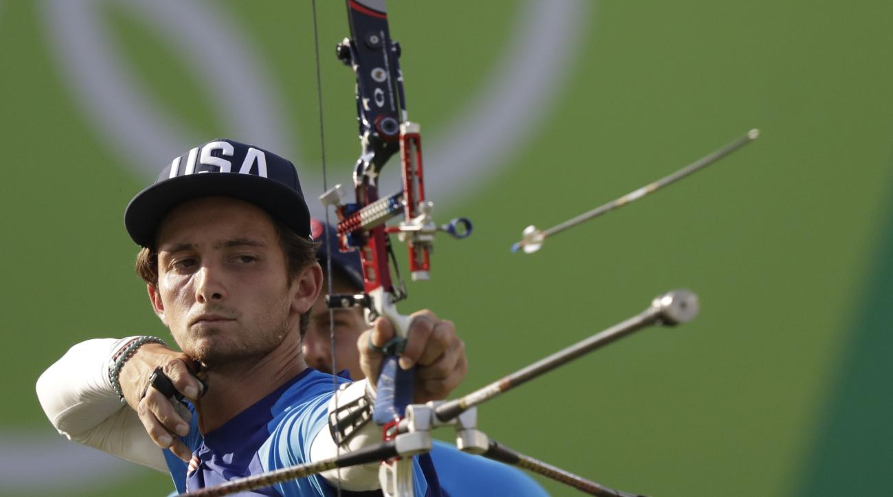 Zach Garrett of the United States releases his arrow during the men's team archery competition at the Sambadrome venue during the 2016 Summer Olympics in Rio de Janeiro, Brazil, Saturday, Aug. 6, 2016.(AP Photo/Natacha Pisarenko)