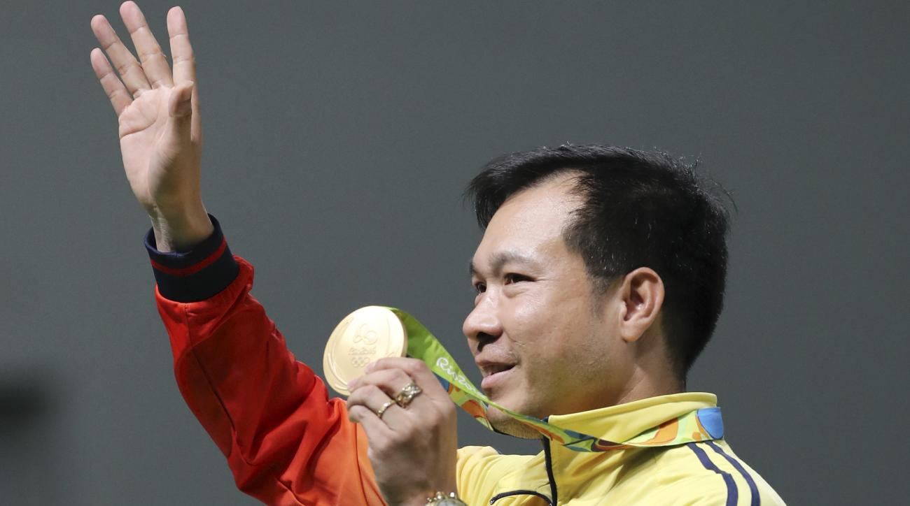 Hoang Xuan Vinh of Vietnam poses for photographers with his gold medal during the award ceremony of the men's 10-meter air pistol event at Olympic Shooting Center at the 2016 Summer Olympics in Rio de Janeiro, Brazil, Saturday, Aug. 6, 2016. (AP Photo/Eug
