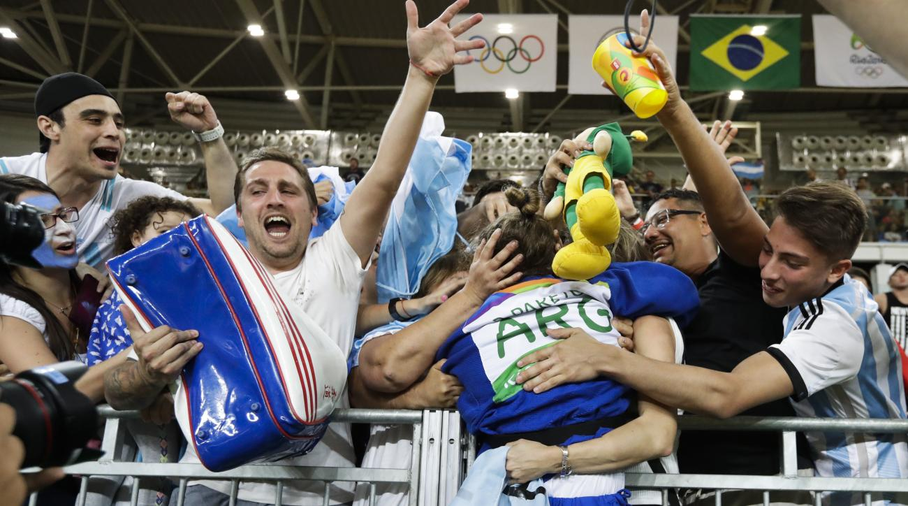 Argentina's Paula Pareto celebrates with supporters after she wind the gold medal in the women's 48-kg judo competition at the 2016 Summer Olympics in Rio de Janeiro, Brazil, Saturday, Aug. 6, 2016. (AP Photo/Markus Schreiber)