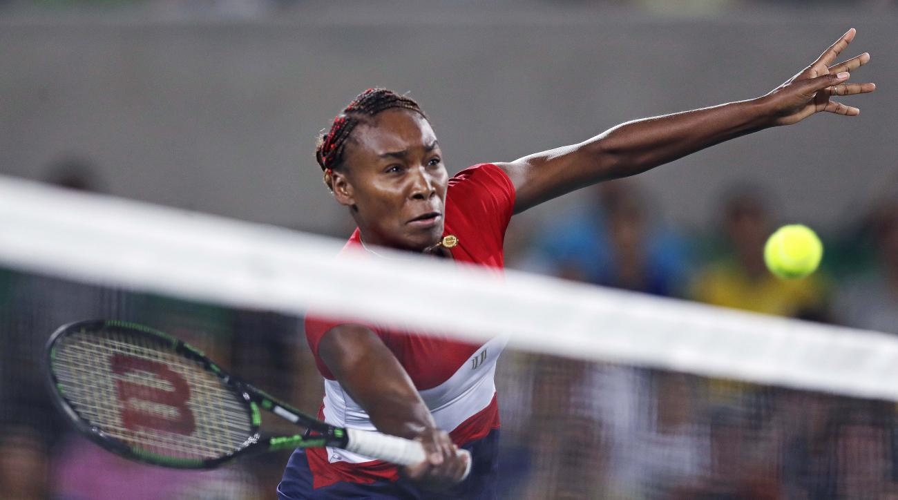 Venus Williams, of the United States, returns a shot at the net against Kirsten Flipkens, of Belarus, at the 2016 Summer Olympics in Rio de Janeiro, Brazil, Saturday, Aug. 6, 2016. (AP Photo/Charles Krupa)