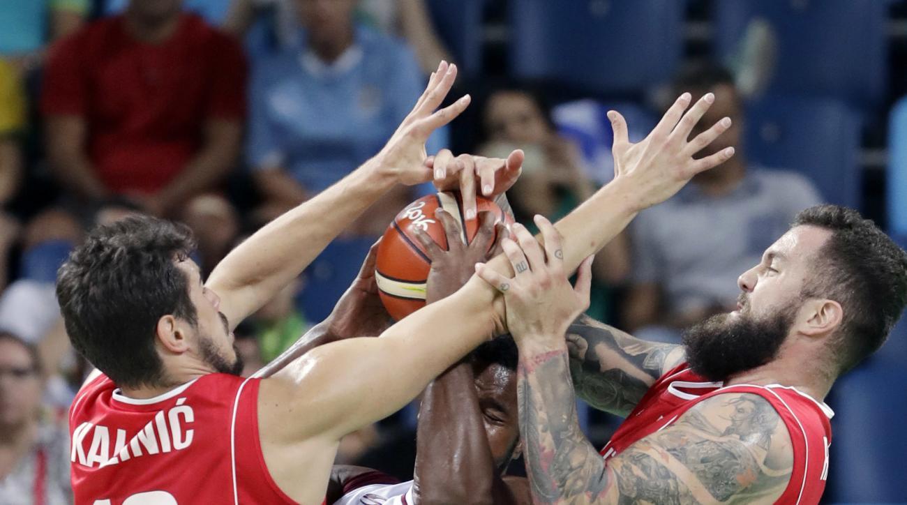 Venezuela's Nestor Colmenares, center, is pressured by Serbia's Nikola Kalinic (10) and Serbia's Miroslav Raduljica, right, during a men's basketball game at the 2016 Summer Olympics in Rio de Janeiro, Brazil, Saturday, Aug. 6, 2016. (AP Photo/Eric Gay)