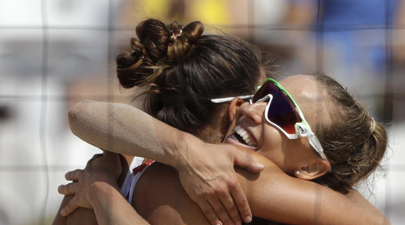 Poland's Monika Brzostek, right, and Kinga Kolosinska celebrate after winning their women's beach volleyball match over the United States at the 2016 Summer Olympics in Rio de Janeiro, Brazil, Sunday, Aug. 7, 2016. (AP Photo/Marcio Jose Sanchez)