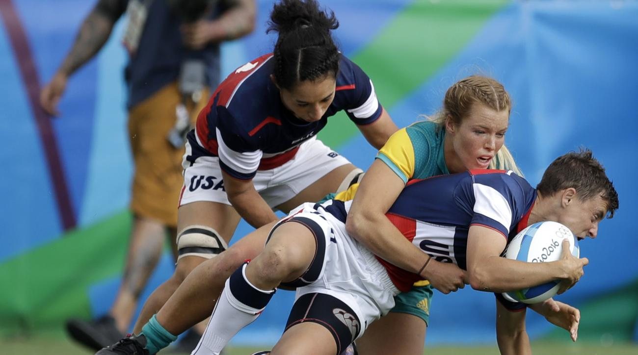 USA's Jessica Javelet, right, is tackled by Australia's Emma Tonegato, back, as teammate Kelly Griffin, watches during the women's rugby sevens match at the Summer Olympics in Rio de Janeiro, Brazil, Sunday, Aug. 7, 2016. (AP Photo/Themba Hadebe)