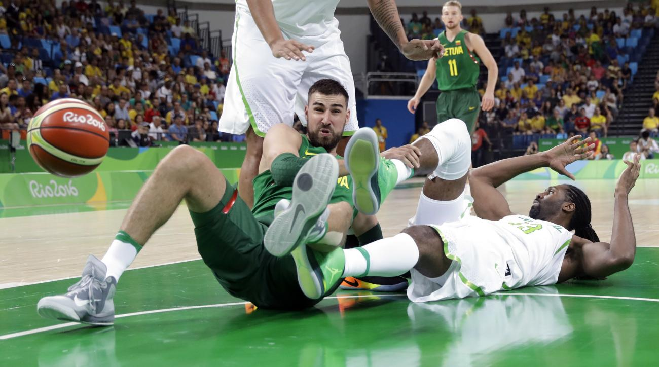 Lithuania's Jonas Valanciunas (17) and Brazil's Nene Hilario (13) crash to the floor as they scramble for the ball during a men's basketball game at the 2016 Summer Olympics in Rio de Janeiro, Brazil, Sunday, Aug. 7, 2016. (AP Photo/Eric Gay)