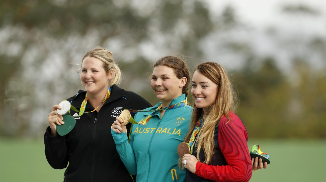 Gold medal winner, Catherine Skinner of Australia, center, poses for a picture with silver medal winner, Natalie Rooney of New Zeland, left, and bronze medalist Corey Cogdell, of the United States, during the victory ceremony for the women's trap event at