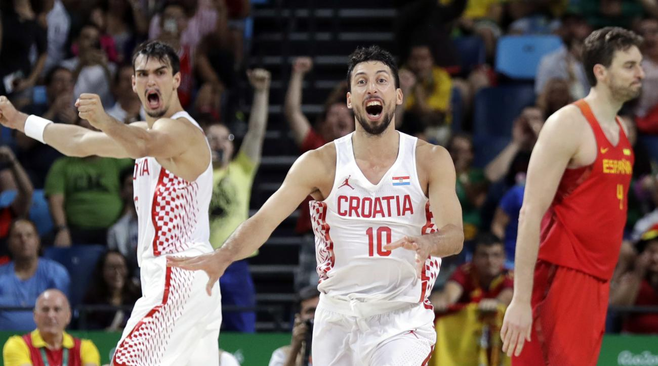 Croatia's Roko Ukic (10) and Dario Saric, left, celebrate after Spain's Pau Gasol, right, failed to make the final shots and Croatia upset Spain in a men's basketball game at the 2016 Summer Olympics in Rio de Janeiro, Brazil, Sunday, Aug. 7, 2016. (AP Ph
