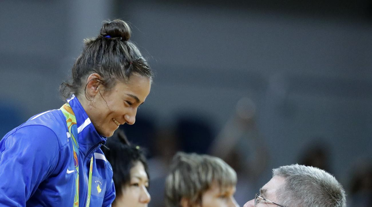Kosovo's Majlinda Kelmendi talks with IOC President Thomas Bach after getting her gold medal for winning the women's 52-kg judo competition at the 2016 Summer Olympics in Rio de Janeiro, Brazil, Sunday, Aug. 7, 2016. Silver medalist Odette Giuffrida, from