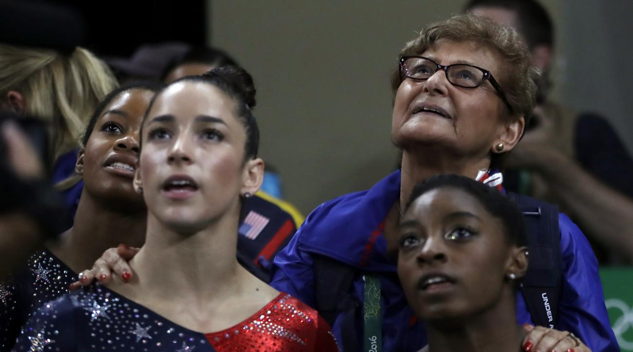 Marta Karolyi, U.S. gymnastics team coordinator, looks at the scoreboard along with, from right, Simone Biles, Aly Raisman and Gabrielle Douglas during the artistic gymnastics women's qualification at the 2016 Summer Olympics in Rio de Janeiro, Brazil, Su