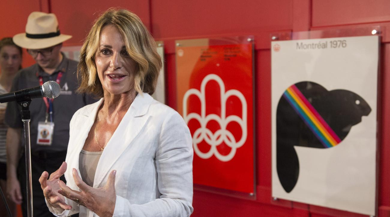 FILE - In this  July 21, 2016, file photo Romania-born gymnastics champion Nadia Comaneci responds to questions as she tours a exhibit marking the 40th anniversary of the Olympic Games in Montreal. Comaneci took to Twitter on August 6, 2016, to correct an