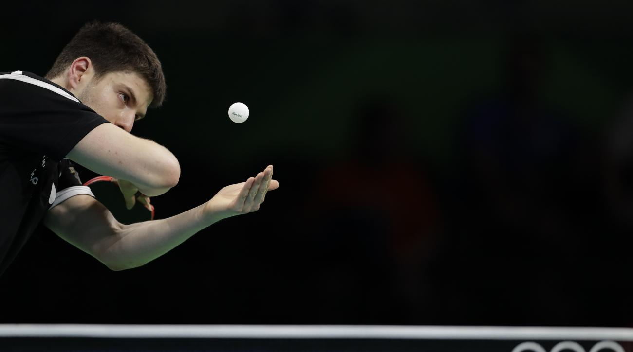 Dimitrij Ovtcharov of Germany eyes the ball as he is playing against Li Ping of Qatar during their table tennis match at the 2016 Summer Olympics in Rio de Janeiro, Brazil, Monday, Aug. 8, 2016.(AP Photo/Petros Giannakouris)