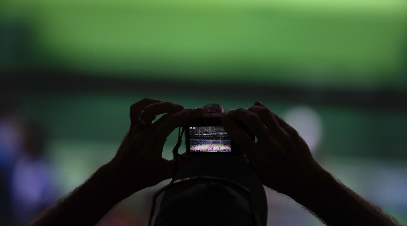A man from the public takes a picture during the women's 57-kg judo competition at the 2016 Summer Olympics in Rio de Janeiro, Brazil, Monday, Aug. 8, 2016. (AP Photo/Natacha Pisarenko)