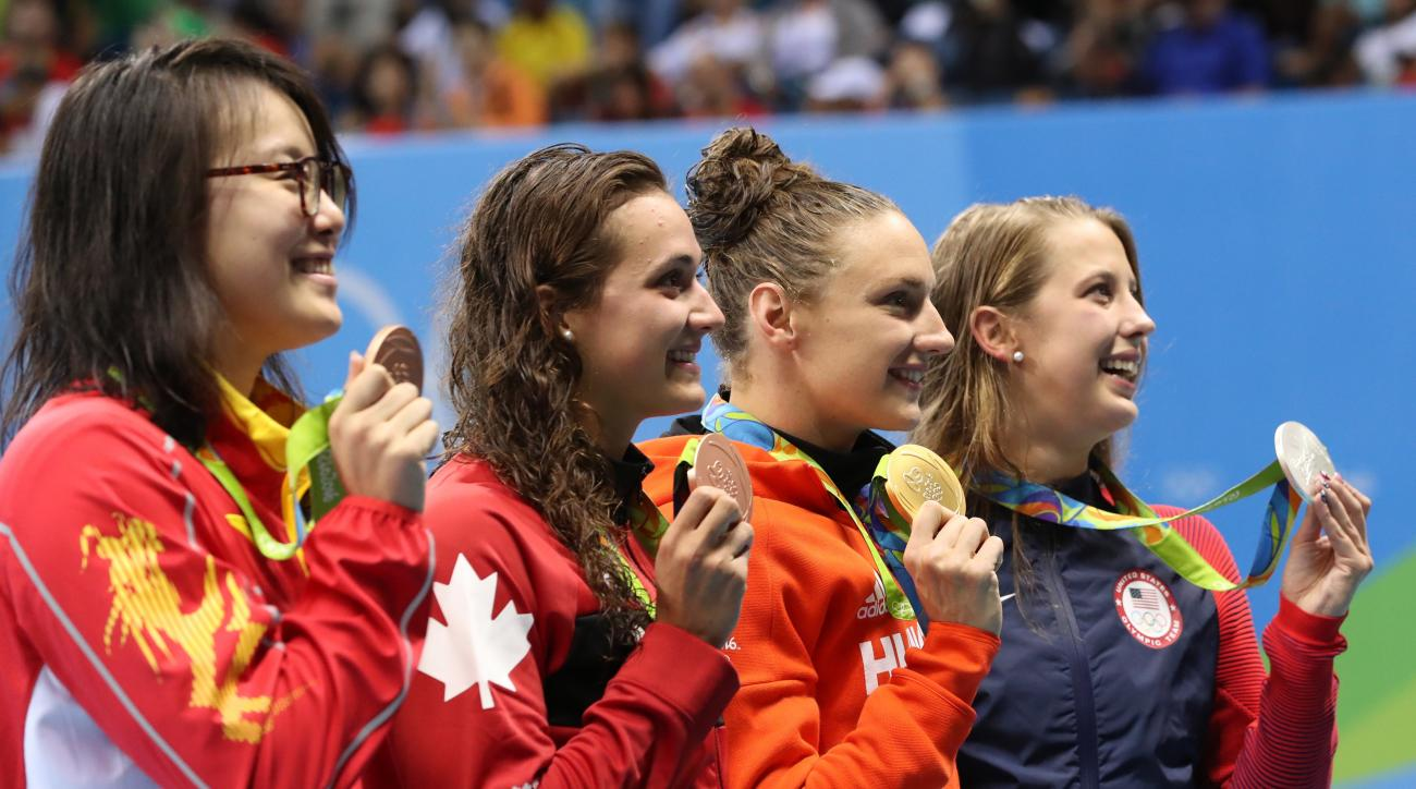 Winner Hungary's Katinka Hosszu, second right, second place United States' Kathleen Baker, right, and joint third place China's Fu Yuanhui, left, and Canada's Kylie Masse during the medal ceremony after the final of the the women's 100-meter backstroke at