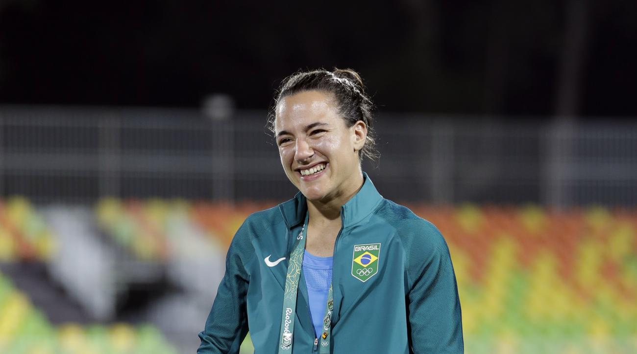 Brazil's Isadora Cerullo, watches on as partner Marjorie Enya entered the pitch and asked her to marry her after the medal ceremony for the women's rugby sevens match at the Summer Olympics in Rio de Janeiro, Brazil, Monday, Aug. 8, 2016. (AP Photo/Themba