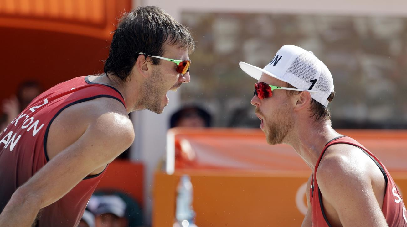 Canada's Ben Saxton, left, and Chaim Schalk celebrate a point over Brazil during a men's beach volleyball match at the 2016 Summer Olympics in Rio de Janeiro, Brazil, Tuesday, Aug. 9, 2016. (AP Photo/Marcio Jose Sanchez)