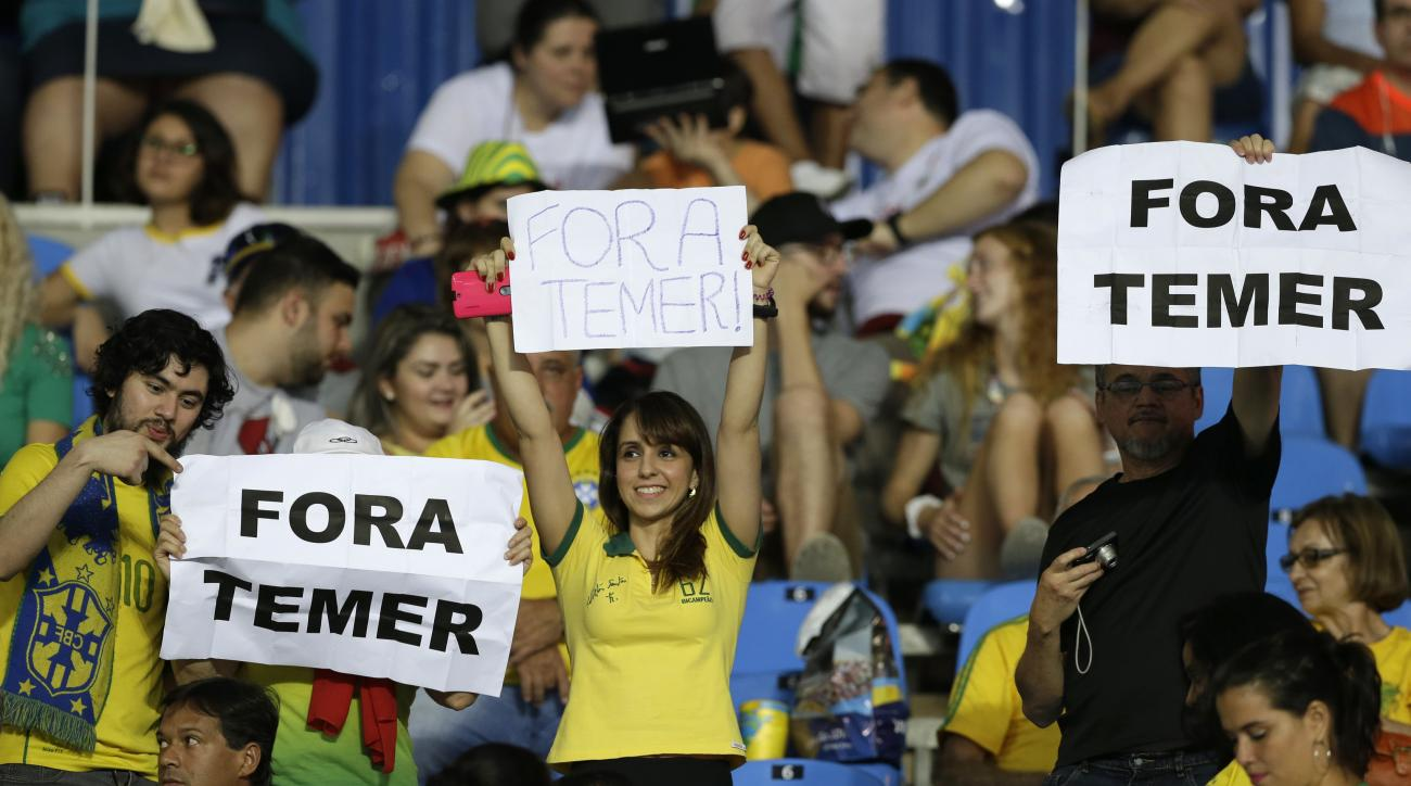 """In this Aug. 6, 2016 photo, fans hold signs that read in Portuguese; """"Temer Out"""" prior to a group E match of the women's Olympic football tournament between Brazil and Sweden at the Rio Olympic Stadium in Rio de Janeiro, Brazil. A court ruling banning the"""