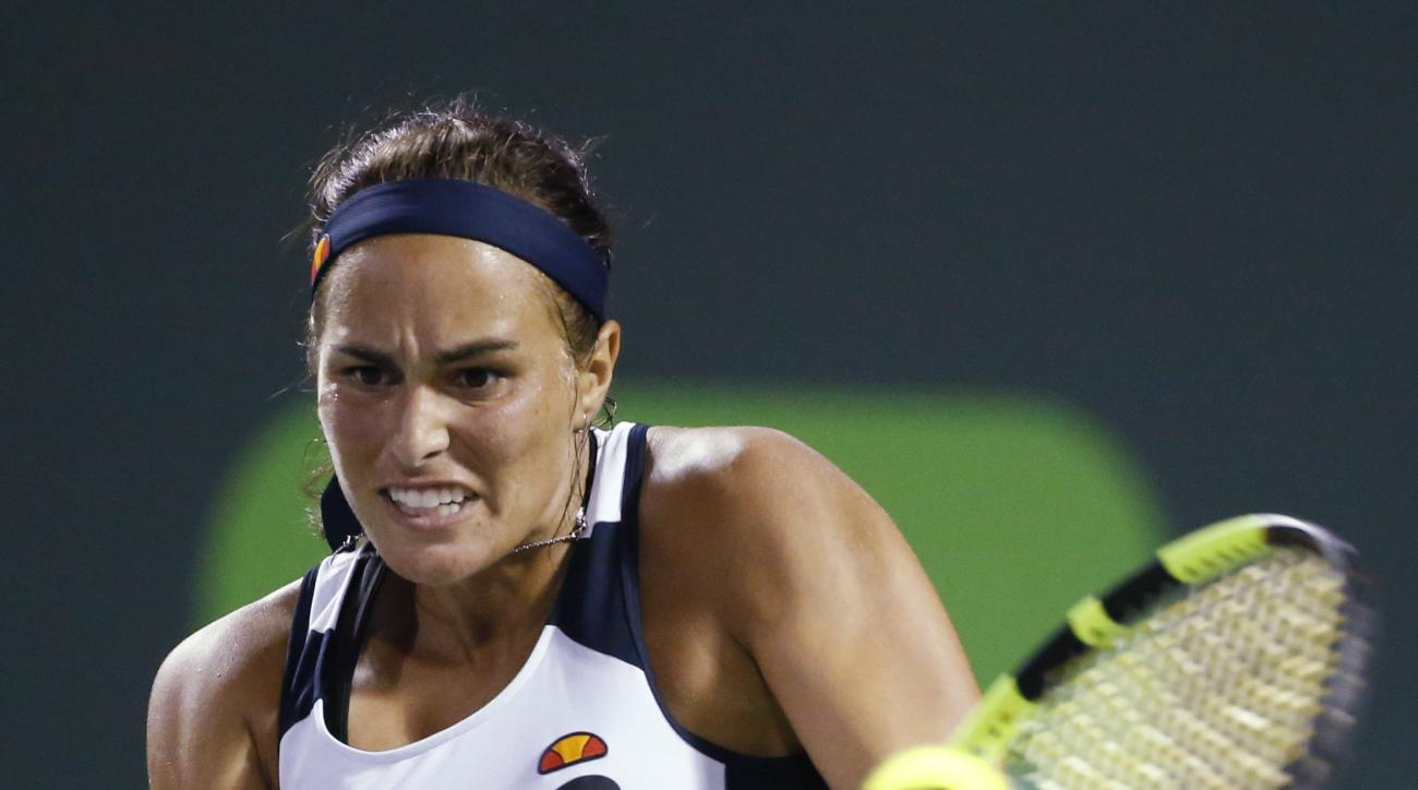Monica Puig, of Puerto Rico, returns a shot from Victoria Azarenka, of Belarus, at the Miami Open tennis tournament, in Key Biscayne, Fla., Friday, March 25, 2016. Azarenka defeated Puig 6-2, 6-4. (AP Photo/Wilfredo Lee)