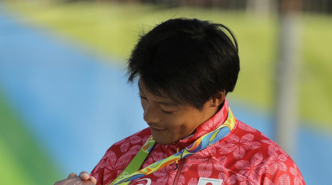 Takuya Haneda, of Japan, looks at his bronze medal during a medal ceremony for the canoe single C1 men's final of the Canoe Slalom at the 2016 Summer Olympics in Rio de Janeiro, Brazil, Tuesday, Aug. 9, 2016. (AP Photo/Jae C. Hong)