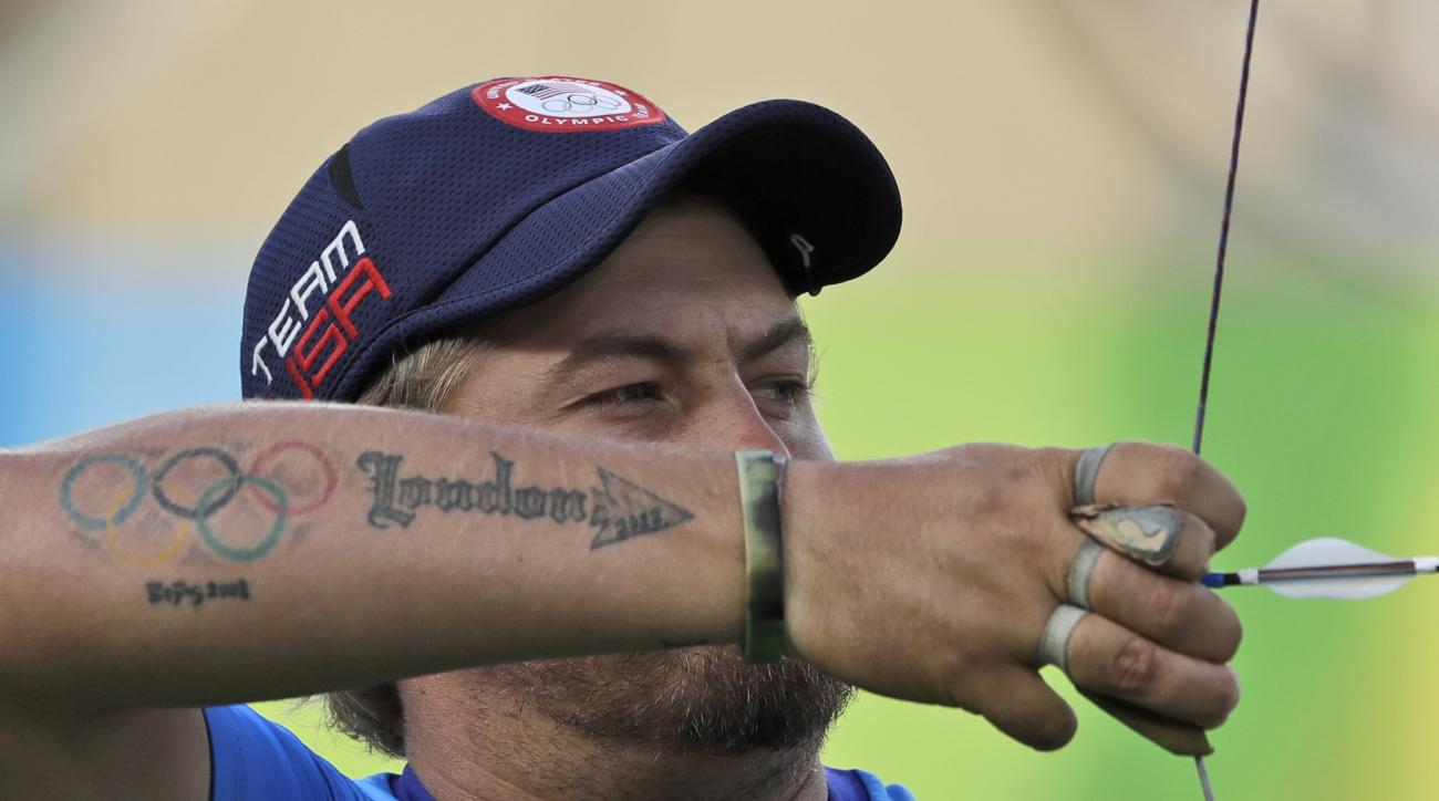 Brady Ellison of the United States, sports a tattoo with the Olympic rings as he releases his arrow during an elimination round of the individual archery competition at the Sambadrome venue during the 2016 Summer Olympics in Rio de Janeiro, Brazil, Tuesda