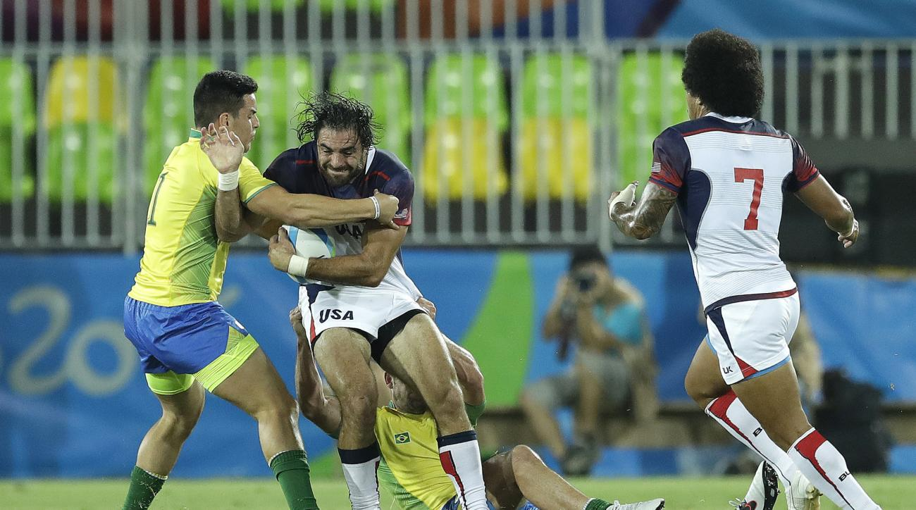 United States's Nate Ebner, second from left, is tackled by Brazil's Daniel Sancery, during the men's rugby sevens match at the Summer Olympics in Rio de Janeiro, Brazil, Tuesday, Aug. 9, 2016. (AP Photo/Themba Hadebe)