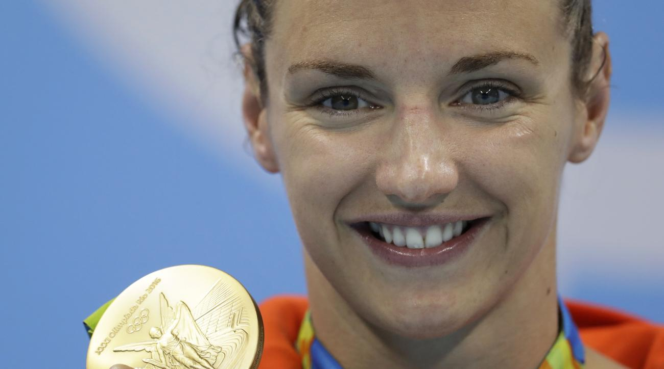 Hungary's Katinka Hosszu shows off her gold medal for the women's 200-meter individual medley final during the swimming competitions at the 2016 Summer Olympics, Wednesday, Aug. 10, 2016, in Rio de Janeiro, Brazil. (AP Photo/Michael Sohn)