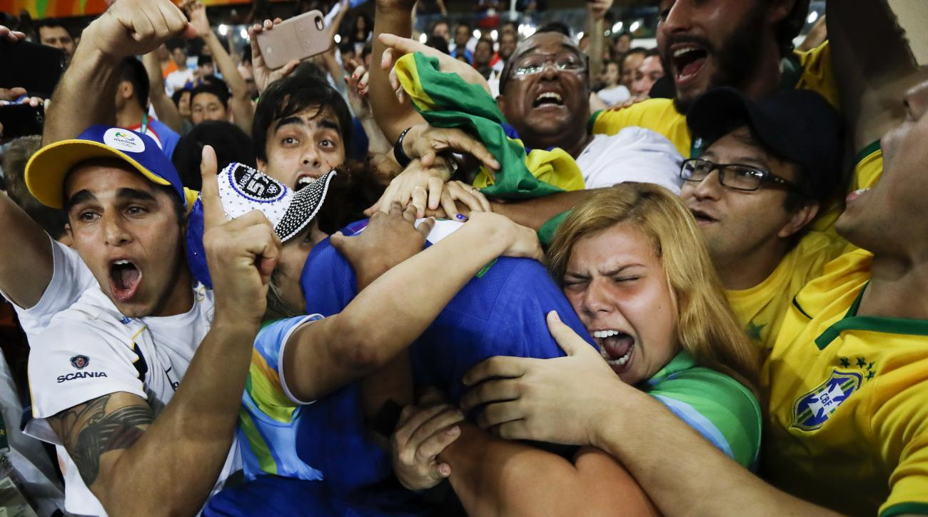FILE - In this Monday, Aug. 8, 2016 file photo, Brazil's Rafaela Silva, center, celebrates with supporters after winning the gold medal of the women's 57-kg judo competition at the 2016 Summer Olympics in Rio de Janeiro, Brazil. Judo champion Silva grew u