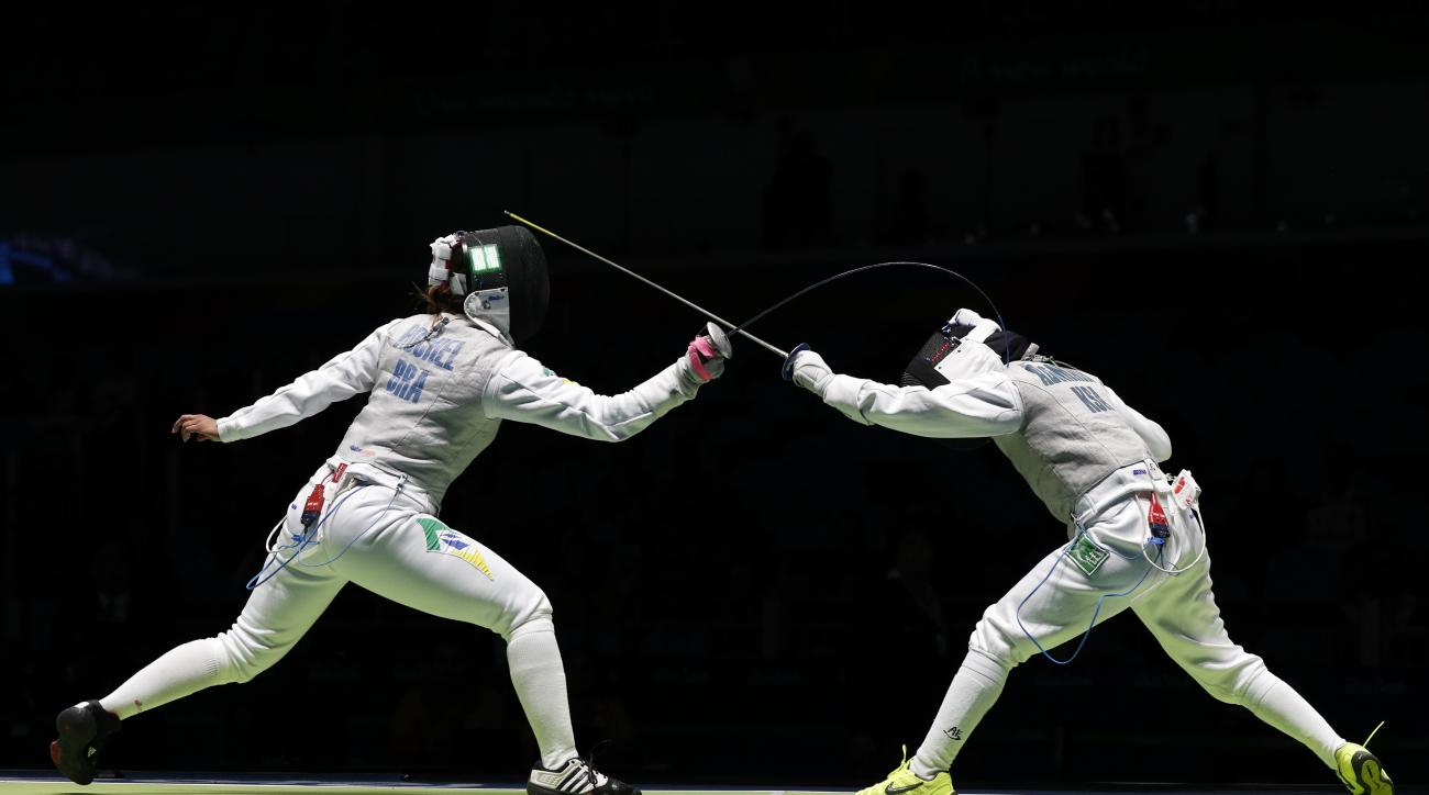 Tais Rochel from Brazil, left, and Lubna Alomair from Saudi Arabia, compete in the women's foil individual fencing event at the 2016 Summer Olympics in Rio de Janeiro, Brazil, Wednesday, Aug. 10, 2016. (AP Photo/Vincent Thian)