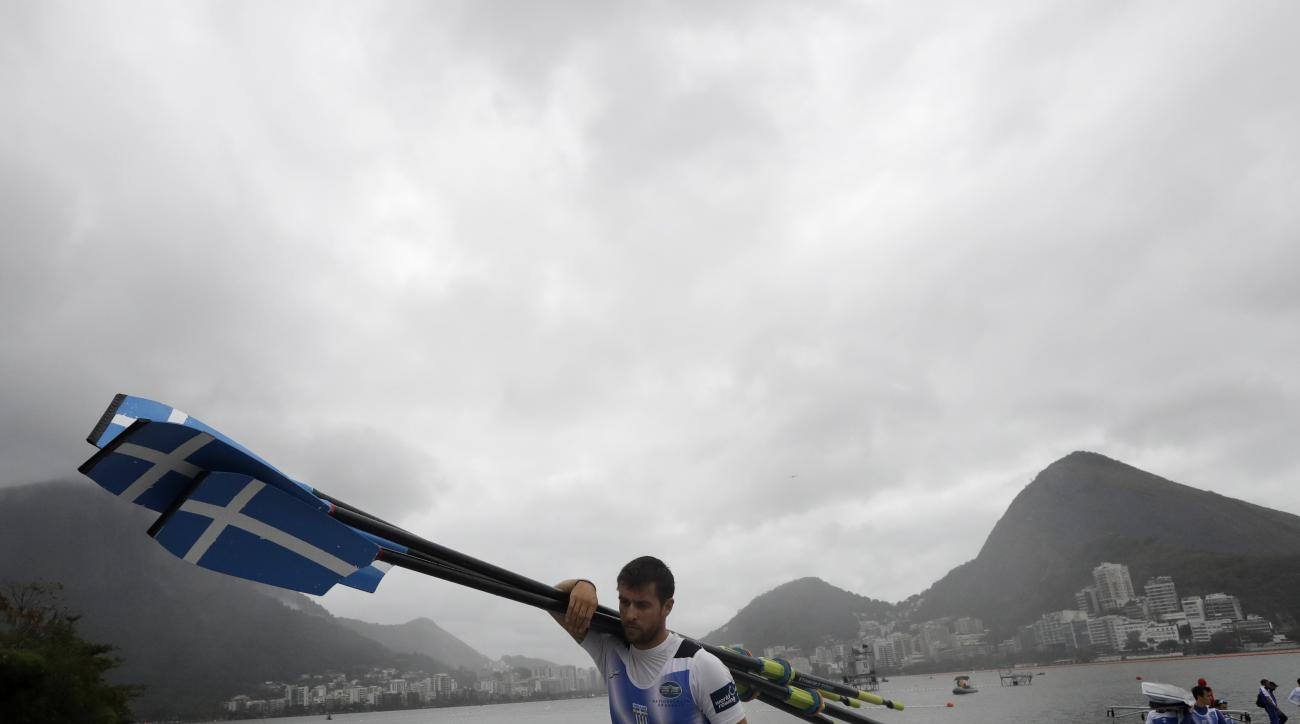 Rowers from Greece remove their boat from the water after a rowing training session during the 2016 Summer Olympics in Rio de Janeiro, Brazil, Wednesday, Aug. 10, 2016. Rowing competition was postponed Wednesday due to weather. (AP Photo/Gregory Bull)