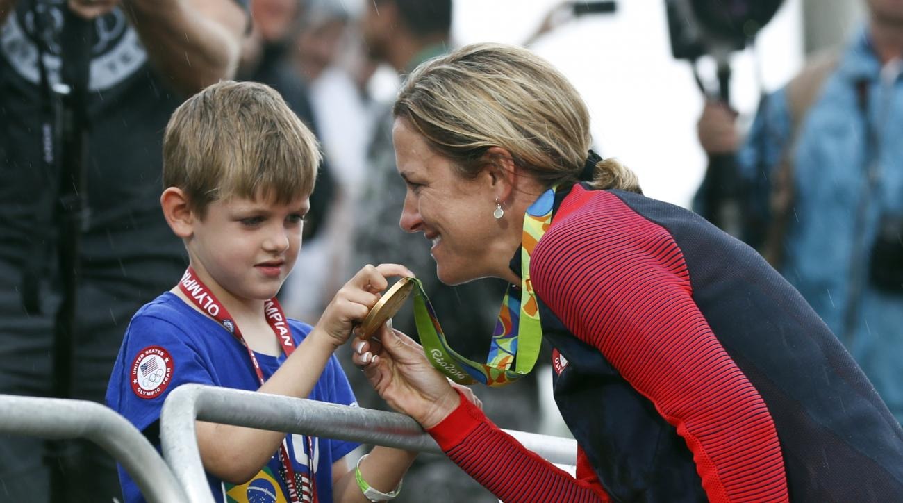Cyclist Kristin Armstrong of the United States, right, shows her gold medal to his son Lucas William Savola after winning the women's individual time trial event at the 2016 Summer Olympics in Pontal beach, Rio de Janeiro, Brazil, Wednesday, Aug. 10, 2016