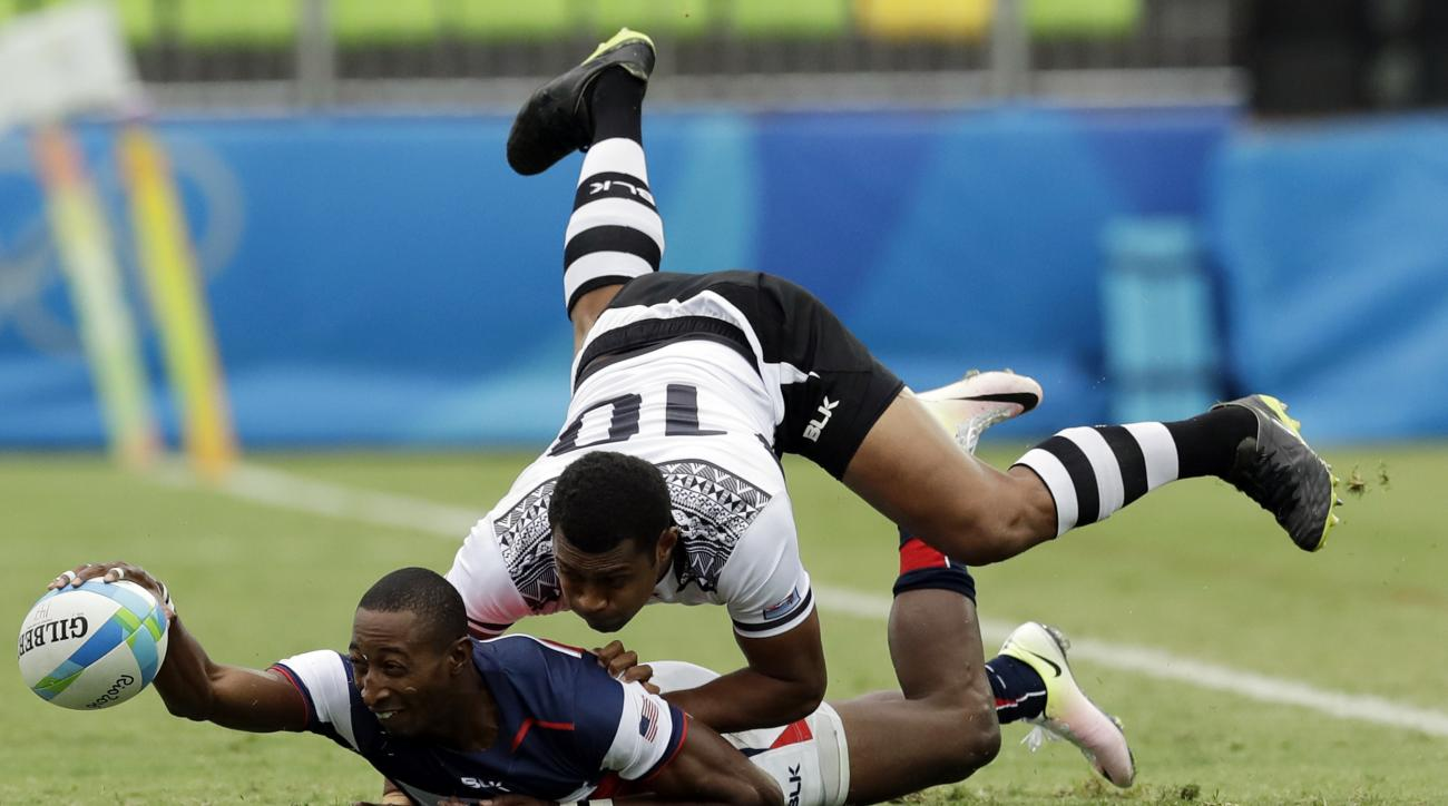 United States's Perry Baker, left, passes the ball as Fiji's Samisoni Viriviri, challenges during the men's rugby sevens match at the Summer Olympics in Rio de Janeiro, Brazil, Wednesday, Aug. 10, 2016. (AP Photo/Themba Hadebe)