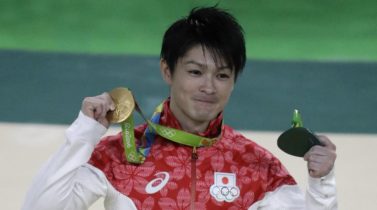 Japan's Kohei Uchimura celebrates on the podium after receiving his gold medal in the artistic gymnastics men's individual all-around final at the 2016 Summer Olympics in Rio de Janeiro, Brazil, Wednesday, Aug. 10, 2016. (AP Photo/Julio Cortez)