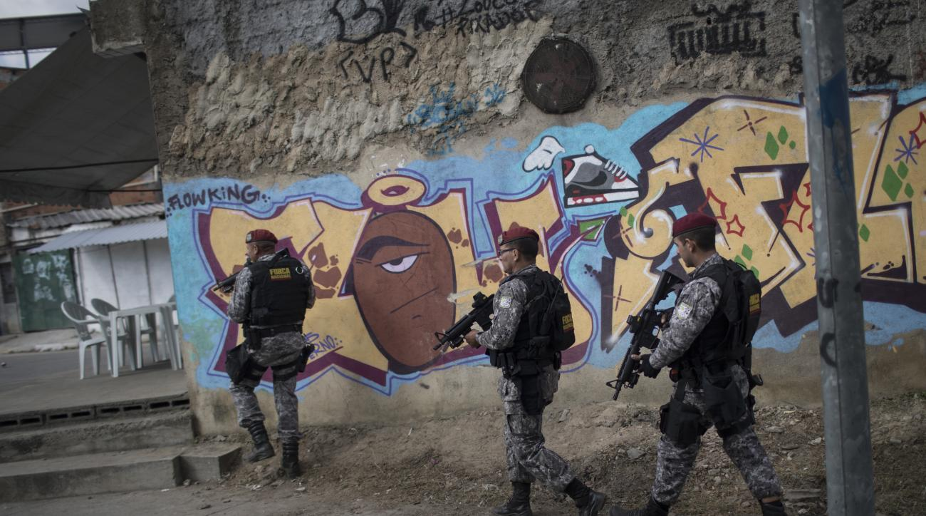 Brazil's national security force officers move inside the Vila do Joao, part of the Mare complex of slums during a police operation in search for criminals during the 2016 Summer Olympics in Rio de Janeiro, Brazil, Thursday, Aug. 11, 2016. A police office