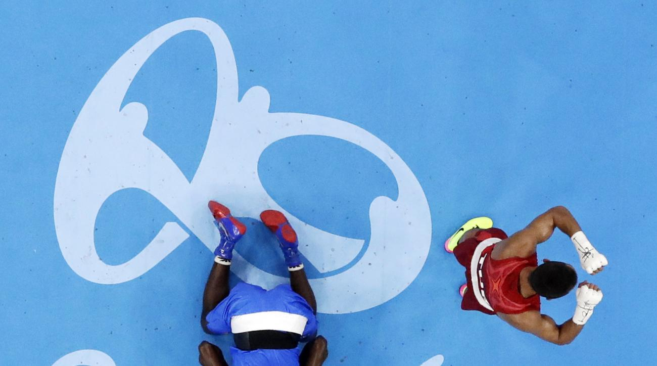 Turkey's Batuhan Gozgec, right, celebrates as he wins the match while Cameroon's Mahaman Smaila kisses the mat during a men's light welterweight 64-kg preliminary boxing match at the 2016 Summer Olympics in Rio de Janeiro, Brazil, Thursday, Aug. 11, 2016.