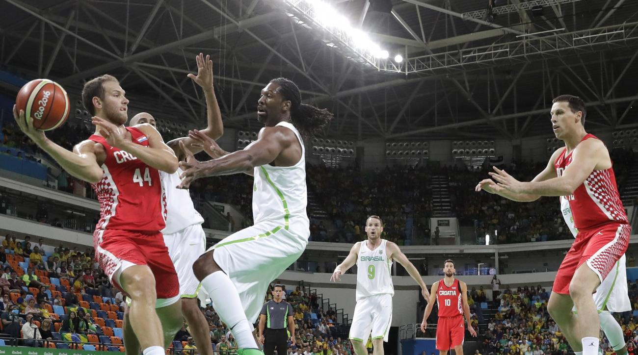 Croatia's Bojan Bogdanovic (44) passes the ball around Brazil's Nene Hilario (13) during a men's basketball game at the 2016 Summer Olympics in Rio de Janeiro, Brazil, Thursday, Aug. 11, 2016. (AP Photo/Eric Gay)