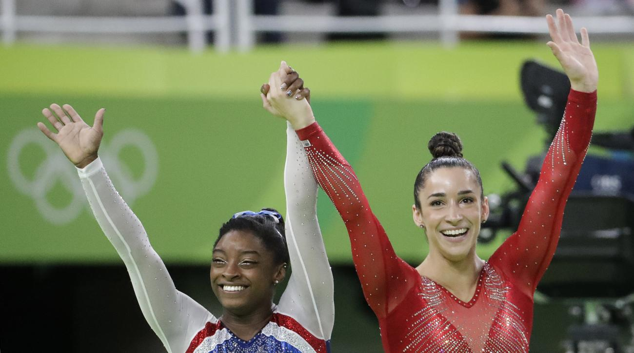 United States' Simone Biles, left, and Aly Raisman wave after winning gold and silver respectively for the artistic gymnastics women's individual all-around final at the 2016 Summer Olympics in Rio de Janeiro, Brazil, Thursday, Aug. 11, 2016. (AP Photo/Da