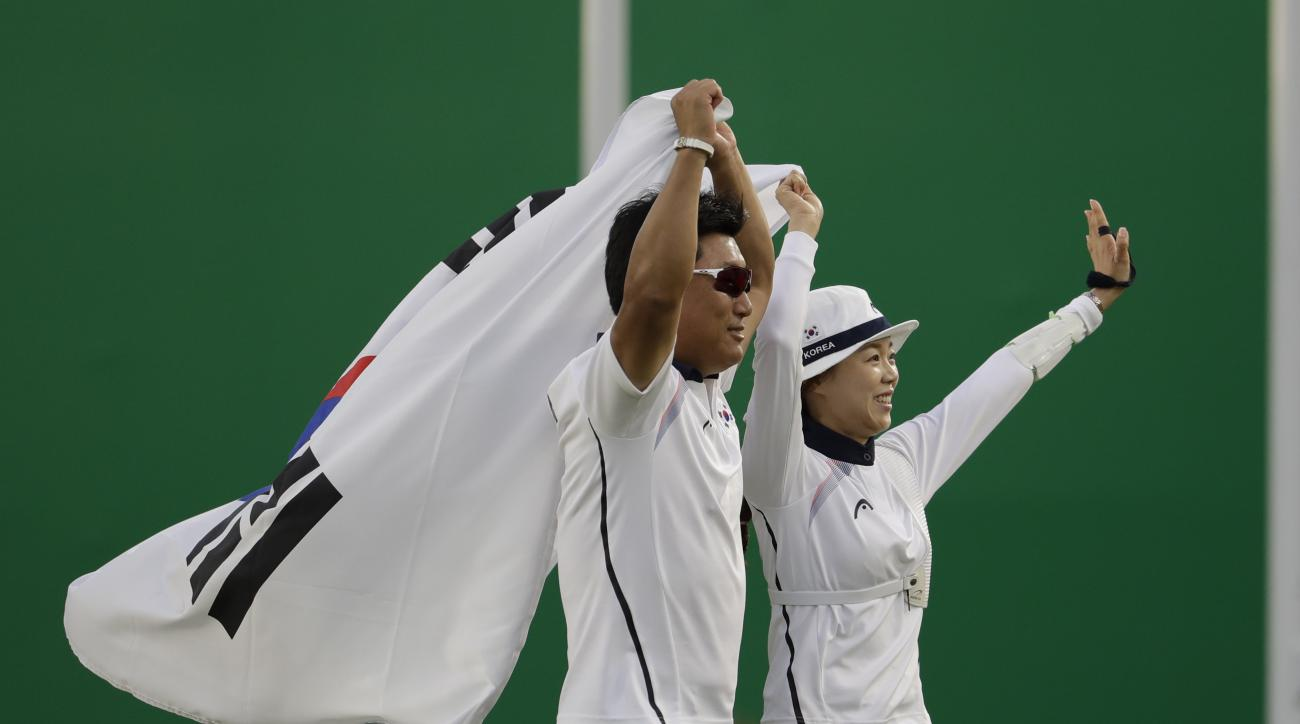 South Korea's Chang Hye-jin, right, celebrates winning gold at the end of the match against silver medalist Lisa Unruh of the women's individual archery competition at the Sambadrome venue during the Summer Olympics in Rio de Janeiro, Brazil, Thursday, Au