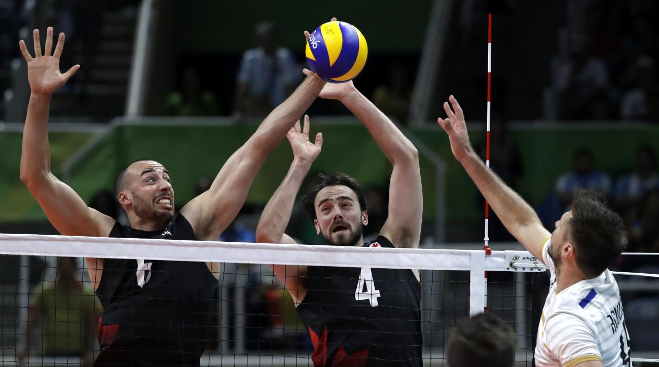 Canada's Justin Duff, left, blocks a spike from France's Antonin Rouzier, right, as teammate Nicholas Hoag watches during a men's preliminary volleyball match at the 2016 Summer Olympics in Rio de Janeiro, Brazil, Thursday, Aug. 11, 2016. (AP Photo/Jeff R