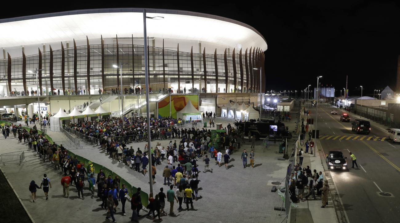 Fans reenter the basketball venue following a controlled explosion at a basketball game between Spain and Nigeria at the 2016 Summer Olympics in Rio de Janeiro, Brazil, Thursday, Aug. 11, 2016. (AP Photo/Eric Gay)