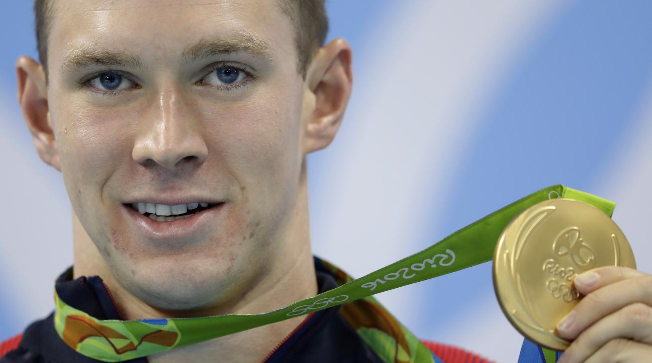United States' Ryan Murphy shows off his gold medal during the medal ceremony for the men's 200-meter backstroke final during the swimming competitions at the 2016 Summer Olympics, Thursday, Aug. 11, 2016, in Rio de Janeiro, Brazil. (AP Photo/Michael Sohn